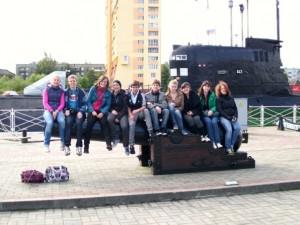 Die Schülerinnen und Schüler sitzen auf einer Kanone