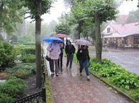Die Teilnehmer der Studienfahrt rennen mit Schirmen durch Rauschen im Regen