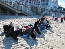 Teilnehmer der Studienfahrt liegen im Sand
